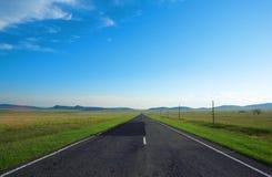 Estrada, nuvens e o céu azul Fotos de Stock