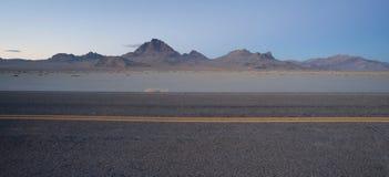 A estrada passa a grande ilha Mountai da prata de planos de sal de Bonneville Fotos de Stock Royalty Free