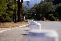 Estrada pavimentada com colunas e árvores imagem de stock royalty free