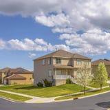 Estrada pavimentada quadrado do quadro ao longo das casas bonitas sob o céu azul com nuvens inchados em um dia ensolarado fotos de stock