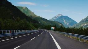 Estrada perto de Graz, Áustria, em junho de 2017: A estrada magnífica em Áustria, nos cumes bonitos do fundo rapidamente filme