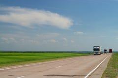 Estrada que atravessa campos fotografia de stock