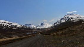 Estrada que conduz à montanha da neve em Islândia Imagem de Stock