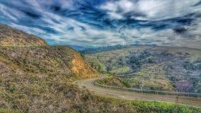 Estrada que curva-se através das montanhas da montanha Céus tormentosos imagens de stock royalty free