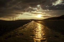 A estrada que desaparece ao horizonte sob o sol irradia a vinda para baixo calha as nuvens tormentosos dramáticas Por do sol na e Imagens de Stock Royalty Free