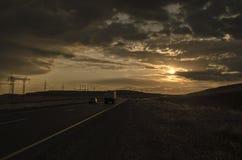 A estrada que desaparece ao horizonte sob o sol irradia a vinda para baixo calha as nuvens tormentosos dramáticas Por do sol na e Foto de Stock