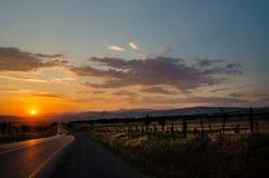 A estrada que desaparece ao horizonte sob o sol irradia a vinda para baixo calha as nuvens tormentosos dramáticas Por do sol na e Imagem de Stock Royalty Free
