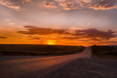 A estrada que desaparece ao horizonte sob o sol irradia a vinda para baixo calha as nuvens tormentosos dramáticas Por do sol na e Fotografia de Stock Royalty Free