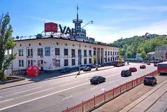 A estrada que passa perto da construção antiga da estação do rio de Kiev em um fundo de árvores verdes Kiev, Ucrânia imagens de stock