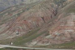A estrada que passa perto do pé da montanha coberta com a vegetação e as listras vermelhas fotos de stock