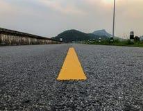 A estrada que tem a listra amarela no meio com backgroun natural foto de stock