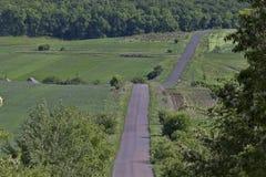 A estrada que vai para baixo, entre os campos Fotografia de Stock Royalty Free