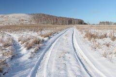 Estrada que vai perto de um monte calvo, Sibéria do automóvel da neve, Rússia Fotos de Stock Royalty Free