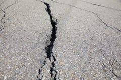 Estrada rachada no fim do asfalto acima foto de stock