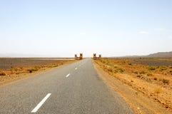 Estrada reta através do deserto Imagem de Stock