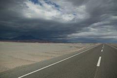 Estrada reta com nuvens Fotos de Stock Royalty Free