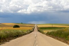 Estrada reta longa na paisagem ondulada com campos cultivados foto de stock