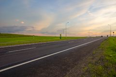 Estrada reta longa que conduz no por do sol imagens de stock royalty free