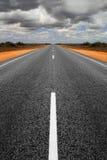 Estrada reta longa que recolhe nuvens de tempestade Fotografia de Stock