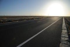 Estrada reta no nascer do sol Imagens de Stock Royalty Free