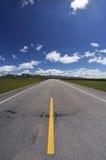 Estrada reta sob o céu azul Imagens de Stock Royalty Free