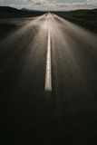Estrada reta vazia de encontro ao sol Fotos de Stock