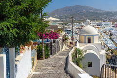 Estrada rochoso à cidade de Thira entre igrejas e casas tradicionais na ilha de Santorini, Grécia Fotos de Stock
