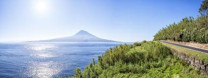 A estrada rodoviária asfaltada em Açores corre ao longo das costas gramíneas do Oceano Atlântico, em um fundo de um vulcão extint Fotografia de Stock