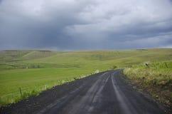 Estrada rural do cascalho abaixo do céu tormentoso imagem de stock royalty free