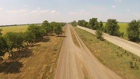 Estrada secundária má, estrada arenosa com as árvores nos lados filme