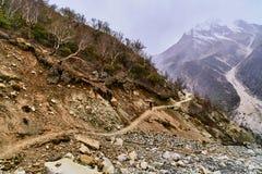 Estrada secundária no céu nebuloso do whit das montanhas Foto de Stock