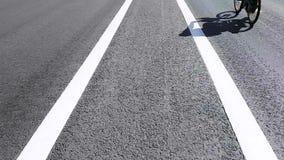Estrada sem close-up dos carros na tira divisora em que o ciclista e um passeio do homem um 'trotinette' el?trico filme