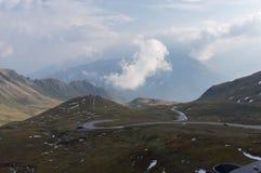 Estrada serpentina e nuvens bonitas altas nas montanhas fotos de stock