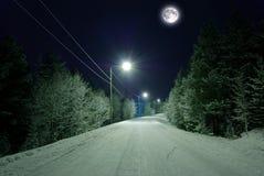 Estrada Snow-covered sob a lua Fotos de Stock Royalty Free