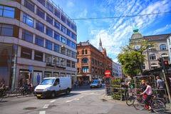 Estrada transversaa no centro da cidade com povos e carros em Copenhaga Fotografia de Stock