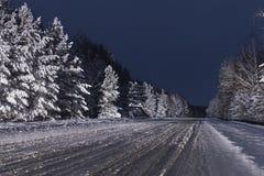Estrada unpeeled do inverno coberto de neve da noite fotografia de stock royalty free