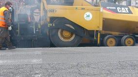 Estrada urbana sob a constru??o, asfaltagem em andamento Trabalhador com uma p? no uniforme azul e alaranjado vídeos de arquivo