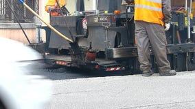 Estrada urbana sob a constru??o, asfaltagem em andamento Trabalhador no uniforme alaranjado filme