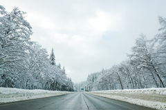 A estrada vazia com nível alto da neve cobriu a paisagem na estação do inverno Imagens de Stock Royalty Free