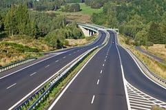 Estrada vazia entre florestas na paisagem Imagens de Stock