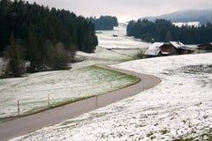 Estradas bonitas entre a neve e a grama verde no tempo de inverno adiantado Fotos de Stock Royalty Free