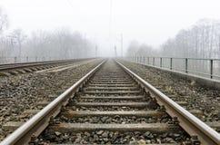 Estradas de ferro que conduzem ao horizonte obscuro Fotografia de Stock