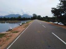 Estradas perto da montanha e do lago corrida da estrada entre a água fotografia de stock