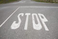 Estradas transversaas com o sinal de parada pintado no asfalto foto de stock