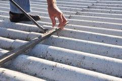 Estragga i chiodi dalle vecchie mattonelle di tetto dell'amianto La riparazione dell'operaio copritore e rimuove le vecchie matto fotografia stock libera da diritti