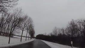 Estralle la cámara de la leva en el coche, nieve en la carretera almacen de metraje de vídeo