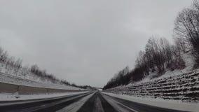 Estralle la cámara en el coche, nieve en la carretera metrajes