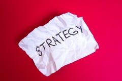 Estratégia da palavra escrita no papel Crumpled no fundo vermelho fotos de stock royalty free