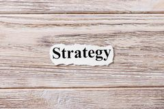 Estratégia da palavra no papel Conceito Palavras da estratégia em um fundo de madeira Imagens de Stock