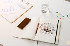 Estratégia empresarial redonda no caderno fotografia de stock